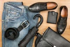 经典黑鞋子、公文包、牛仔裤和伞在木地板上 库存照片
