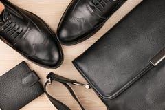 经典黑鞋子、公文包和钱包在木地板上 库存照片