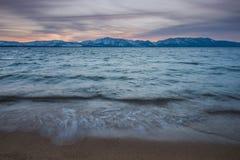 从内华达海滩采取的美好的太浩湖日落和斯诺伊山峰长的曝光,南太浩湖 免版税库存照片
