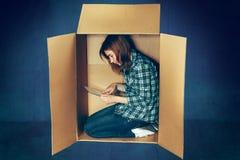 内向概念 妇女坐在箱子里面和与膝上型计算机一起使用 免版税库存照片