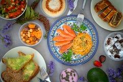 内圆角三文鱼的水多的部分服务用米,菜沙拉, hummus,坚果,鲕梨三明治,巧克力甜点,坚果饼 Gr 免版税库存照片