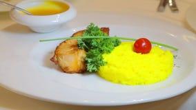 内圆角油煎了与米一道配菜的鱼  煮沸的米和鱼片用调味汁 股票录像