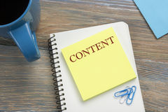 内容,网上概念 与消息和咖啡杯的笔记薄 在书桌台式视图的办公用品 免版税图库摄影