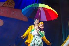 内盖夫,啤酒舍瓦,以色列-女演员和儿童的剧院演员希伯来语的在阶段与一把大明亮的伞在圆点 免版税库存照片