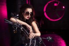 黑内衣、脚跟和太阳镜的深色的性感的妇女在红灯的演播室在摩托车 户内 免版税库存照片