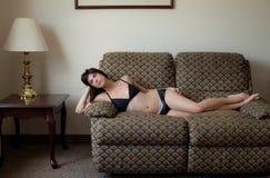 内衣的妇女在长沙发 免版税库存图片