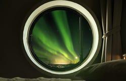 内部圈子窗口在卧室有美好的北极光极光Borealis视图在晚上 免版税库存图片