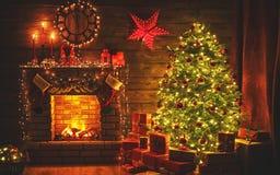 内部圣诞节 不可思议的发光的树,在黑暗的壁炉礼物 免版税库存图片