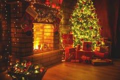 内部圣诞节 不可思议的发光的树,在黑暗的壁炉礼物 免版税库存照片