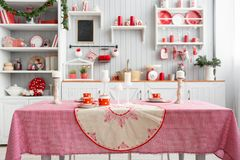 内部浅灰色的厨房和红色圣诞节装饰 在家准备午餐在厨房概念 在桌上的焦点 免版税库存图片