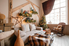 内部现代家庭客厅的镇静图象装饰了圣诞树和礼物,沙发,用毯子盖的桌 免版税库存照片