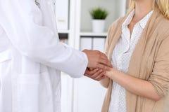 再保证她的女性患者的医生的手 医德和信任概念 库存图片