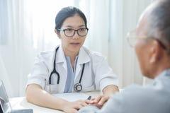 再保证资深男性患者的女性医生 图库摄影