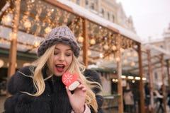 再拿着有味道的圣诞节姜饼的快活的白肤金发的妇女 图库摄影