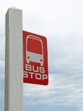 再红色和白色公共汽车站标志灰色风雨如磐的天空 库存照片
