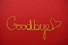 再见丝带问候和心脏在红色背景 库存图片