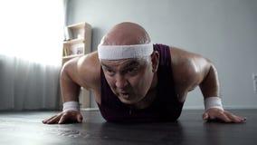 冒汗与设法微弱的胳膊的肌肉的男性在家做俯卧撑,锻炼 免版税图库摄影