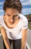 冒汗在跑的疲乏的赛跑者女孩与太阳以后 库存图片