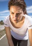 冒汗在跑的疲乏的赛跑者女孩与太阳以后 免版税库存图片