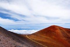 冒纳凯阿火山山顶,在夏威夷的海岛上的一座休眠火山 惊人盘旋在云彩上的美好的红色石峰顶, 免版税库存照片