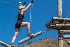 冒险上升的绳索公园-一个少妇沿日志和绳索走在高度以山和蓝色s为背景 库存照片