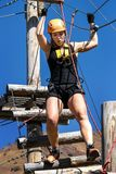 冒险上升的绳索公园-防护齿轮的一个少妇通过在绳索模拟器的轨道 的训练登山家 库存图片