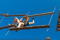 冒险上升的绳索公园-防护齿轮的一个少妇通过在绳索模拟器的轨道 免版税库存图片