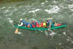 冒险的两个人在冲的河急流乘独木舟 库存图片