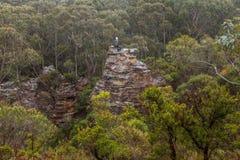 冒险的女性徒步旅行者爬上了在山bushland的岩石塔上 库存照片