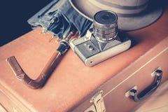 冒险背景双筒望远镜小船概念梯子水 与葡萄酒帽子和伞的老影片照相机在老棕色手提箱 被定调子的葡萄酒 免版税库存图片