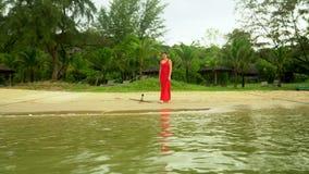 冒险路农村跟踪的背景汽车 在海岛的海岸的传统蓝色渔船 一件红色礼服的妇女在走 股票视频