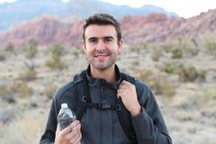 冒险,旅行,旅游业、远足和人概念-供以人员拿着远足在沙漠的水瓶和黑背包 库存照片