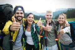 冒险,旅行,旅游业、远足和人概念-小组有背包和地图的微笑的朋友户外 免版税图库摄影