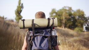 冒险,旅行,旅游业、远足和人概念 走与背包的后侧方traking的观点的朋友由小山 股票录像