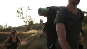 冒险,旅行,旅游业、远足和人概念 走由与巨大的背包的小山的两个远足者 疲乏的面孔女孩 股票视频