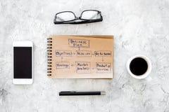 写一个经营计划 有剪影的办公室工作场所在灰色背景顶视图的笔记本 库存图片