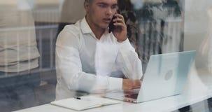 写下企业信息的年轻商人在他的在玻璃状咖啡馆的膝上型计算机 慢动作,午饭时间 股票录像
