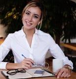 写下她的想法和喝coffe的聪明的妇女在咖啡馆 免版税库存图片