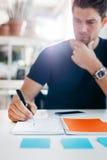 写下注意事项的商人在办公室日志 免版税图库摄影