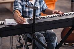写下笔记的有残障的音乐家 库存图片