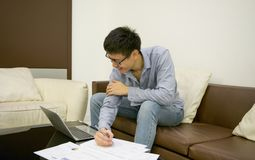 写与膝上型计算机的亚洲商人一个文件在生存roo 库存照片