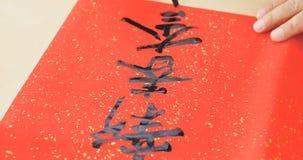 写中国书法写与意味h的词组的纸 免版税库存照片