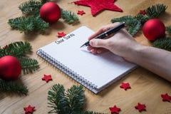写亲爱的圣诞老人在与圣诞节装饰和f的一个笔记薄 免版税库存图片