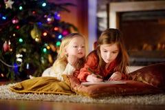 写信的两个逗人喜爱的妹给圣诞老人由壁炉在圣诞节 库存照片