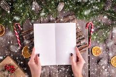 写信的女性手给圣诞老人在木背景 免版税图库摄影