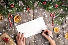 写信的女性手给圣诞老人在木背景 免版税库存照片