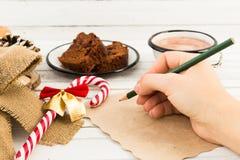 写信的妇女手给圣诞老人 免版税库存照片