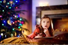 写信的逗人喜爱的小女孩给圣诞老人由壁炉在圣诞节 免版税图库摄影