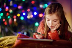 写信的逗人喜爱的小女孩给圣诞老人由壁炉在圣诞节 库存图片