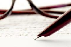 写信,玻璃的葡萄酒钢笔后边 库存照片